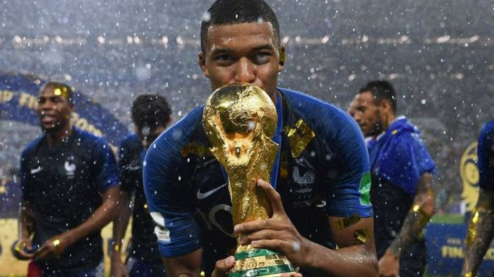Pemain Perancis Kylian Mbappe mencium trofi juara usai mengalahkan Kroasia pada laga babak final Piala Dunia 2018 di Stadion Luzhniki, Moskwa, Minggu (15/7/2018) atau Senin dini hari WIB. Perancis mengulangi kesuksesan 20 tahun lalu dan keluar sebagai juara Piala Dunia 2018 usai menundukkan Kroasia dengan skor 4-2.(AFP PHOTO/FRANCK FIFE)