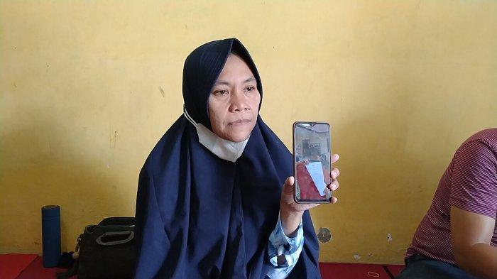 Lia Pratiwi, ibu korban, memperlihatkan dokumentasi foto anaknya, Muhammad Reza Aulia (10), saat membuat laporan di kantor polisi, Selasa (15/6/2021). Muhammad Reza Aulia meninggal dunia akibat gigitan anjing milik tetangganya.