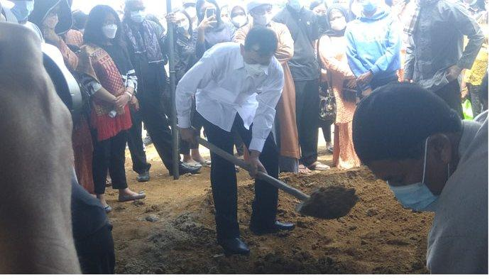 Mantan Bupati Simalungun JR Saragih (tengah), menutup liang makam ibunya yang dimakamkan di Desa Kutambaru, Kecamatan Munte, Selasa (14/9/2021).