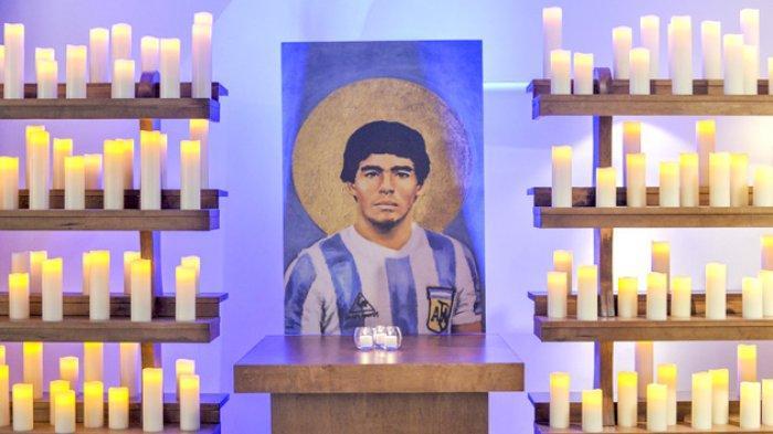 Lilin dinyalakan di sisi lukisan Diego Maradona di gereja pemujaan untuk dirinya di Kota Buenos Aires, Argentina.