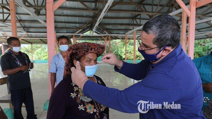 Territory Sales Manager XL Axiata area Karo-Langkat, Maf'ul Taufiq memberikan masker kepada warga Desa Tigapancur, Kecamatan Simpangempat, Karo, Sabtu (20/2).TRIBUN MEDAN/RISKI CAHYADI