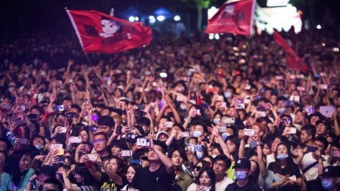 Masyarakat China dengan sedikit yang menggunakan masker saat menonton Strawberry Music Festival di Wuhan pada Sabtu (1/5/2021). [STR/AFP](STR/AFP)