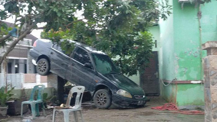 Mobil tersangkut di pagar rumah akibat hantaman banjir di Medan, Jumat (4/12/2020)