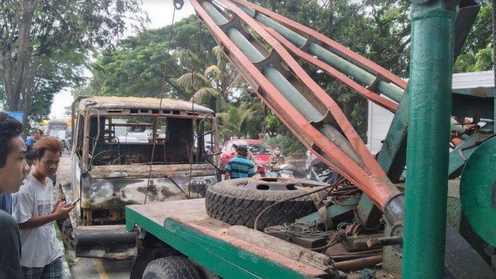 Mobil truk kontainer yang terbakar di Jalan Asrama Kecamatan Medan Helvetia dievakuasi menggunakan mobil derek, Sabtu (18/9/2021)