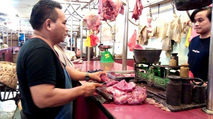 Pedagang daging sapi bernama Edy saat memotongi daging yang hendak dijualnya, Minggu (9/5/2021).(TRIBUN MEDAN/YUFIS)