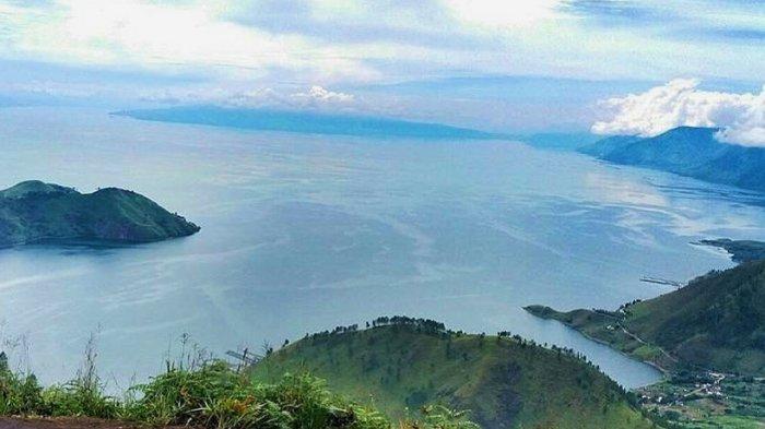 Pemandangan Danau Toba dan bukit savana dari puncak Bukit Gajah Bobok
