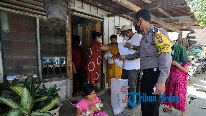 BERITA FOTO Bripka Putra masuk Gang Untuk Membantu Panitia Bagikan Daging Kurban ke Rumah Warga