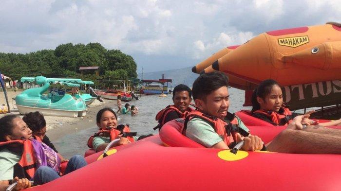 Pengunjung dari Kota Medan bermain Donat Boat di Pantai Lumban Bulbul kawasan Balige, Kabupaten Toba
