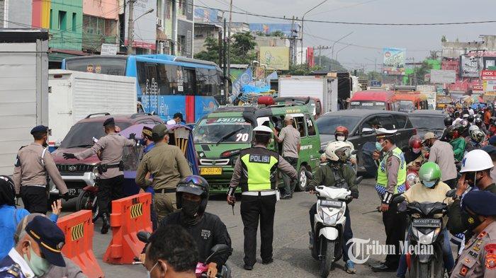Personel gabungan dari TNI, Polri dan Satpol PP melakukan penyekatan Pembatasan Kegiatan Masyarakat (PPKM) Darurat di Kampung Lalang Jalan Gatot Subroto, Medan, Sumatera Utara, Kamis (15/7/2021). Penyekatan tersebut dalam rangka mengurangi mobilitas warga demi mengurangi angka penyebaran COVID-19 selama pemberlakuan PPKM Darurat di Kota Medan.TRIBUN MEDAN/RISKI CAHYADI