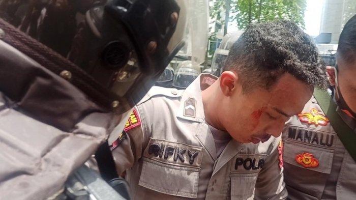 PETUGAS terluka saat mengamankan aksi unjuk rasa berujung ricuh di kantor DPRD Sumut, Kamis (8/10/2020)