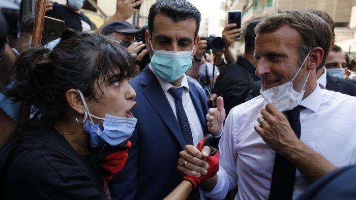 Presiden Perancis, Emmanuel Macron mendengarkan ocehan seorang penduduk saat dia mengunjungi jalan yang hancur di Beirut, Lebanon, Kamis 6 Agustus 2020.