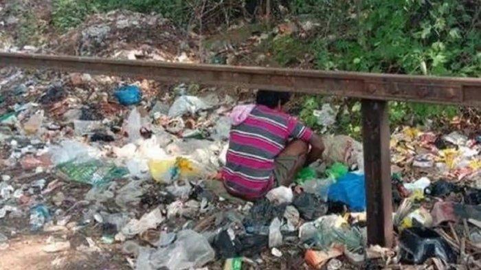 Akibat lockdown, seorang pria India nampak memungut makanan di tumpukan sampah.