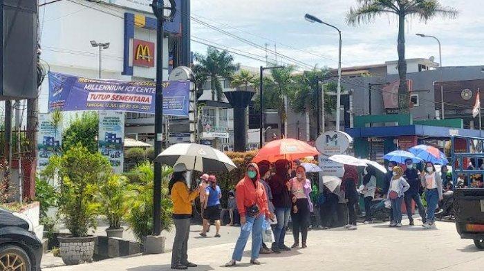 Puluhan tukang servis dan sales handphone turun ke Jalanan Kapten Muslim, Kelurahan Dwi Kora, Kecamatan Medan Helvetia akibat Plaza Millenium ICT Medan tutup di Masa PPKM Darurat, Senin (19/7/2021).