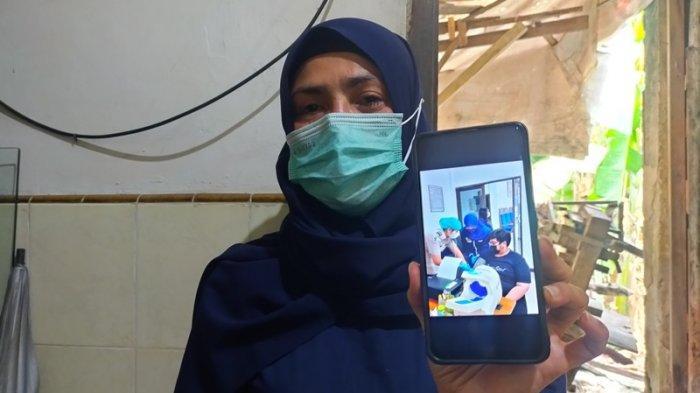 Rahma Dewi (42) ibunda Irwin Perdana Nasution memperlihatkan foto anaknya saat divaksin