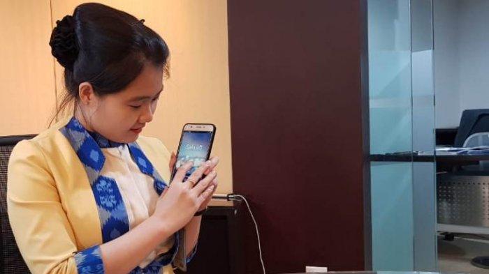 Customer Service BCA KCU Medan, Pretty menunjukkan Sakuku pada ponselnya di Bank BCA Jalan Diponegoro, Medan, Kamis (9/5/2019).