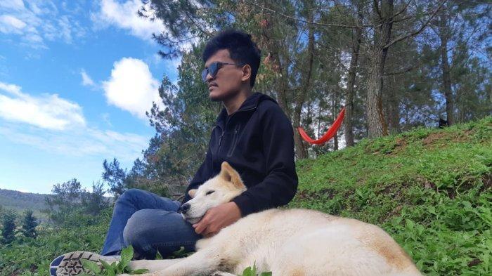 Salah seorang wisatawan bermain bersama anjing