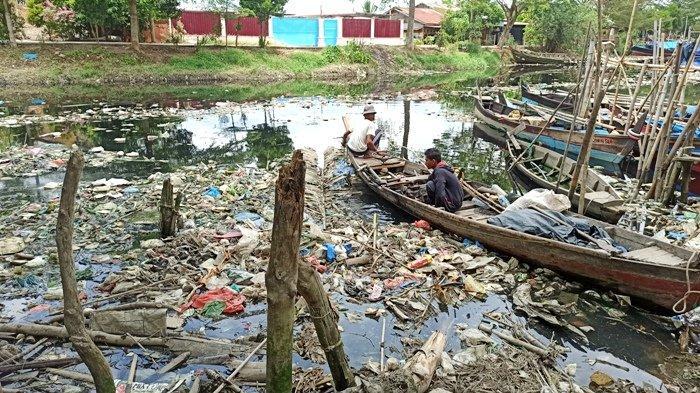 Nelayan yang sedang menyusun perahu di bawah jembatan yang melintasi Sungai Bederah, Jalan Kapten Rahmad Buddin, Kelurahan Terjun, Kecamatan Medan Marelan, Kamis (24/3/2021). Sungai yang kotor membuat nelayan bertahun-tahun kesulitan mencari nafkah.(TRIBUNMEDAN/RECHTIN)