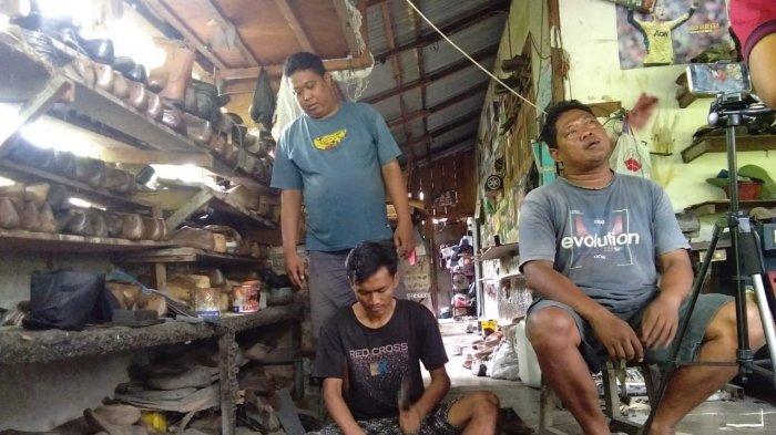Seorang konsumen tengah melihat produk sepatu bunut di salah satu toko, di Jalan Lintas Sumatera, Kisaran, Sabtu (14/9/2019)