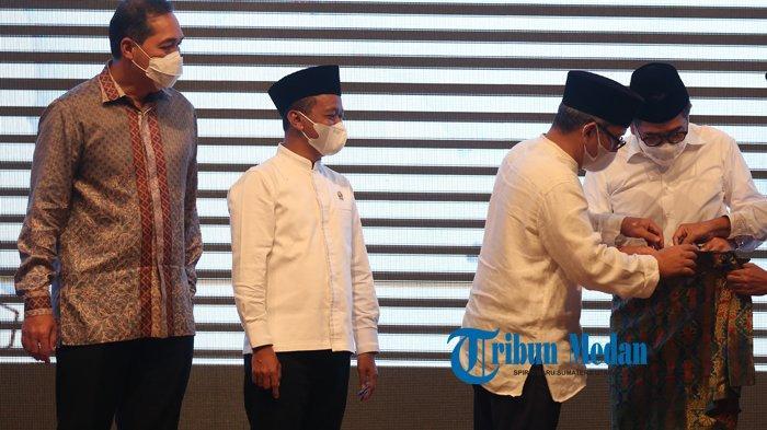 Ketua Umum Kadin Sumatera Utara Ivan Iskandar Batubara (dua kanan) memakaikan kain tradisional khas Sumut kepada Wakil Ketua Umum Kamar Dagang dan Industri (Kadin) Indonesia Bidang Pengembangan Pengusaha Nasional Arsjad Rasjid (kanan), disaksikan oleh Menteri Perdagangan Muhammad Lutfi (kiri) dan Menteri Investasi/BKPM Republik Indonesia Bahlil Lahadalia (dua kiri) pada Buka Puasa Bersama Kadin Sumut di Hotel Adimulia, Medan, Sumatera Utar, Jumat (30/4/2021).TRIBUN MEDAN/RISKI CAHYADI