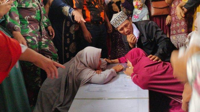 Sri Dewi (Baju Merah) memeluk peti yang berisikan Jasad Lisa