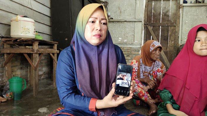 Sutiah menunjukan foto Yunus semasa hidup dari telepon genggam miliknya