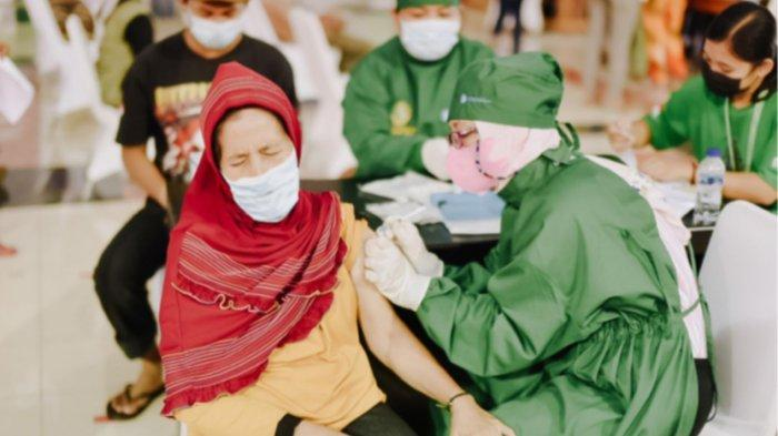 Tenaga medis sedang melakukan vaksinasi kepada salah satu peserta di Pekan Raya Sumatera Utara.