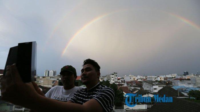 Dua pria berswafoto dengan latar belakang rumah penduduk di Medan, Sumatera Utara, Rabu (7/29/2020). Bank Tabungan Negara (BTN) menggenjot produk layanan bank untuk mendukung pembiayaan Kredit Kepemilikan Rumah (KPR) dengan meningkatkan layanan transaksi digital.TRIBUN MEDAN/RISKI CAHYADI