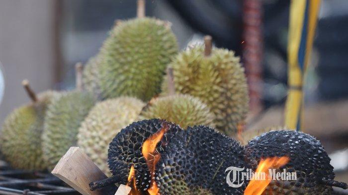 Pedagang mempersiapkan durian bakar pesanan dari pembeli di Jalan Bromo, Medan, Sumatera Utara, Jumat (27/8/2021). Buah durian yang menjadi salah satu primadona yang disantap dengan cara dibakar itu dijual dengan harga Rp25.000-Rp50.000 per butir.TRIBUN MEDAN/RISKI CAHYADI