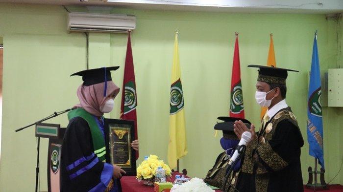 Rektor UISU, Dr.H. Yanhar Jamaluddin, MAP mengucapkan selamat kepada salah satu mahasiswa berprestasi saat pelaksanakan wisuda UISU Periode II TA 2020/2021 yang dipusatkan di Auditorium UISU Jalan SM Raja Medan, Sabtu (28/8).