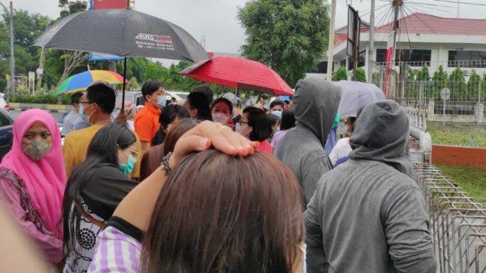 VAKSINASI MASSAL - Warga kota Medan sedang menunggu di depan pintu gerbang Lanud Soewondo untuk mengikuti vaksinasi massal. Mereka kecewa lantaran sudah dua jam menunggu dan hujan-hujanan justru tak mendapat izin untuk masuk. Pangkalan TNI AU, Soewondo, Medan Sumatera Utara, Kamis (3/06/2021). (Tribun-medan.com/ Fredy Santoso)