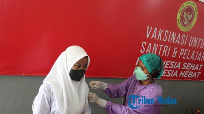 Petugas menyuntikkan vaksin COVID-19 dosis kedua kepada pelajar di SMA Negeri 1, Medan, Sumatera Utara, Selasa (21/9/2021). Badan Intelijen Negara (BIN) Daerah Sumatera Utara menggelar vaksinasi dosis kedua untuk 1500 pelajar SMA.TRIBUN MEDAN/RISKI CAHYADI