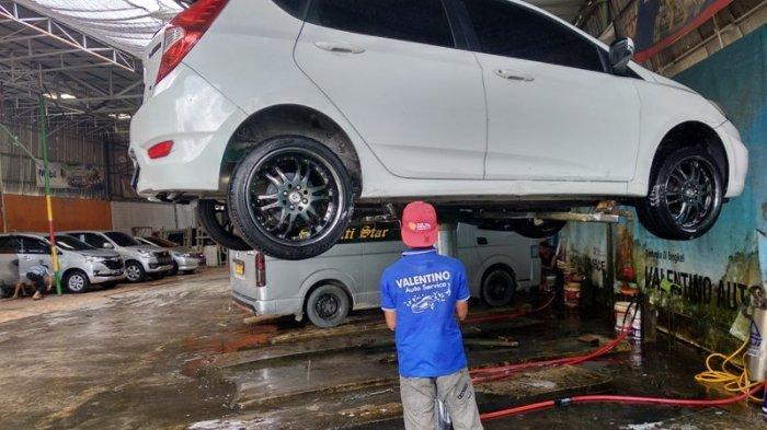 KARYAWAN Valentino Auto Service sedang melakukan pengerjaan mobil pelanggan.