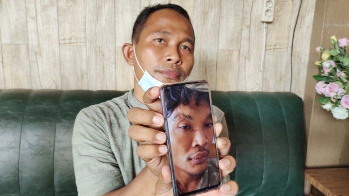 Wahyudi menunjukan foto anak buahnya yang diduga dipukuli oleh anggota PM Lanal TBA di Kecamatan Sungai Kepayang, Selasa (15/6/2021).