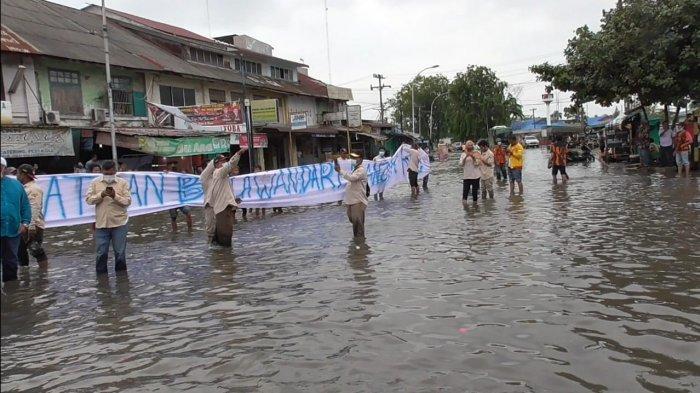 Warga Belawan unjuk rasa di tengah genangan banjir rob di Jalan Sumatera dekat pintu masuk Pelabuhan Belawan, akhir April lalu.