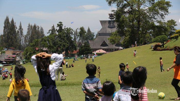 Sejumlah pengunjung menikmati suasana padang rumput hijau di Bukit Kubu, Brastagi, Sumatera Utara, Minggu (5/8/2019).TRIBUN MEDAN/RISKI CAHYADI