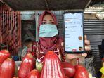ariyanti-penjual-rujak-di-simpang-jodoh-saat-menunjukkan-aplikasi-gofood.jpg