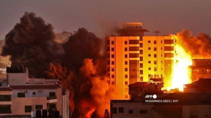 Asap mengepul dari gedung Hanadi di Gaza City pasca serangan udara yang dilakukan pasukan Israel pada 11 Mei 2021.