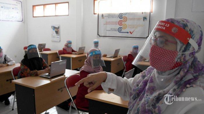 Siswa SMK PGRI 13 Surabaya melakukan simulasi belajar-mengajar pada era new normal yang digelar pihak sekolah, di Kota Surabaya, Jawa Timur, Rabu (17/6/2020). Simulasi digelar agar siswa paham dan tahu proses belajar-mengajar saat new normal dan nanti saat diperbolehkan belajar-mengajar secara tatap muka. Proses belajar-mengajar secara tatap muka saat new normal memperhatikan dengan ketat protokol kesehatan, di antaranya harus cuci tangan, penggunaan hand sanitizer, dan diperiksa suhu tubuhnya sebelum masuk kelas, serta penggunaan face shield (pelindung wajah) baik untuk siswa maupun guru. Surya/Ahmad Zaimul Haq