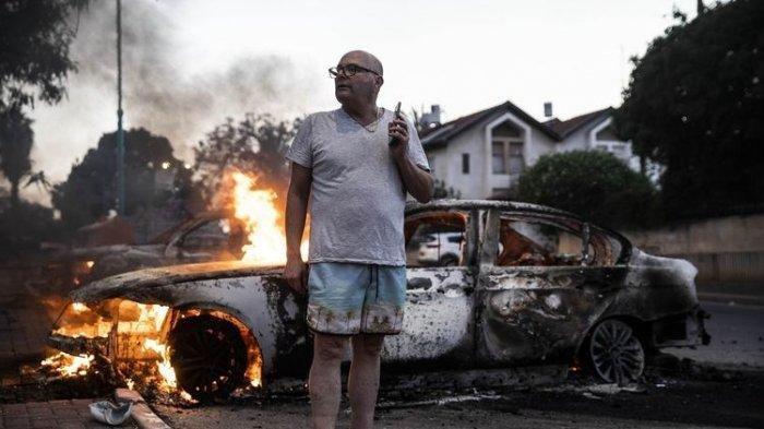 Jacob Simona berdiri di depan mobilnya yang terbakar dalam kerusuhan antara etnis Arab dan polisi di kota Israel, Lod, pada 11 Mei 2021.