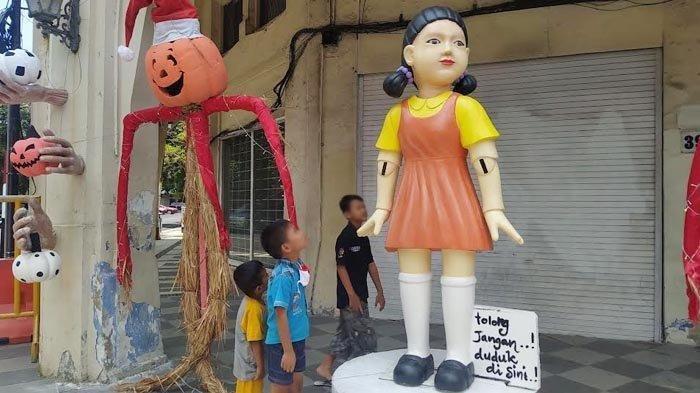 Penampakan boneka raksasa Lampu Merah khas Squid Game yang berdiri di salah satu sudut Jalan Tunjungan, Surabaya, Jumat (8/10/2021) sebelum diangkut Satpol PP.