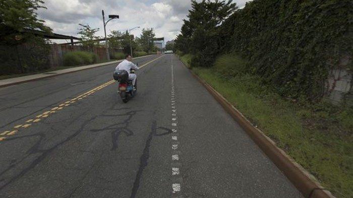 Pria berbaju putih itu tampak telah melihat bahwa dia sedang 'dikejar' oleh mobil Google Street View