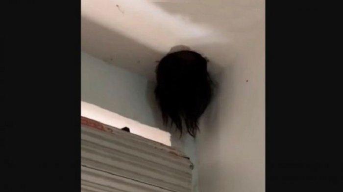 Rambut panjang menjuntai dari lubang di atap rumah