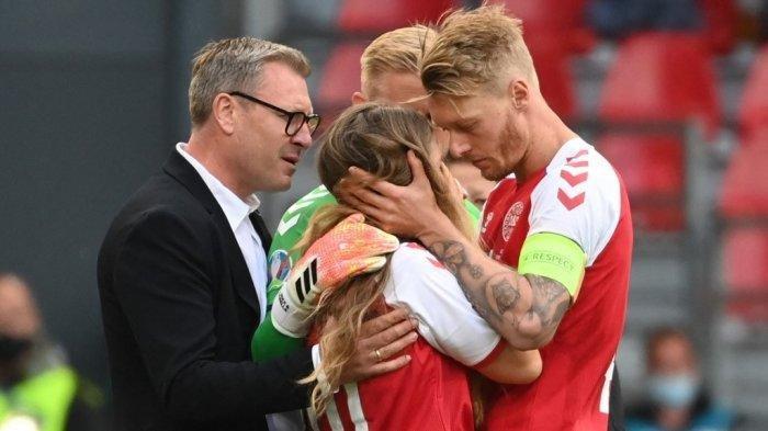 Sabrina Kvist Jensen (tengah), partner dari pemain tengah Denmark Christian Eriksen, dipeluk oleh bek Denmark Simon Kjaer (kanan) saat ia bereaksi setelah Eriksen pingsan selama pertandingan sepak bola Grup B UEFA EURO 2020 antara Denmark dan Finlandia di Stadion Parken di Kopenhagen pada 12 Juni 2021.