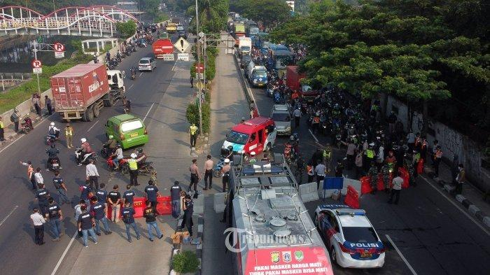 Suasana penyekatan pembatasan menuju Jakarta di Jalan Daan Mogot, Kalideres, Jakarta Barat, Senin (5/7/2021). Polisi melakukan penyekatan di 63 titik wilayah di Jadetabek untuk membatasi mobilitas warga saat Pemberlakuan Pembatasan Kegiatan Masyarakat (PPKM) Darurat yang berlangsung hingga 20 Juli 2021.