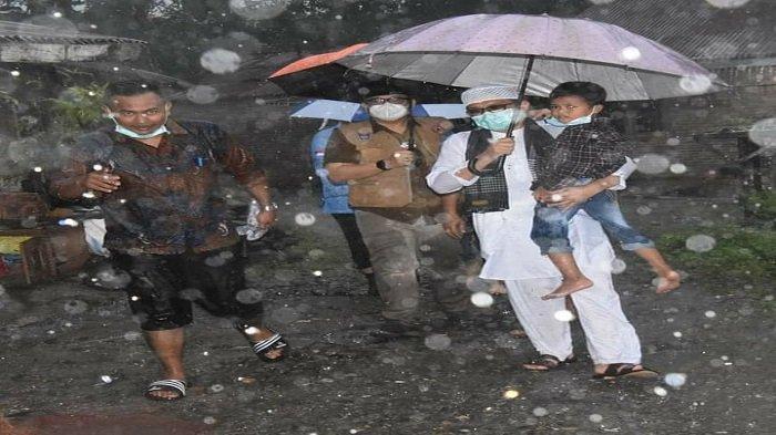 Wali Kota Padang, Hendri Septa menggendong seorang bocah saat ditengah hujan deras saat menyambangi warganya di Kampuang Kalawi, Kelurahan Lubuk Lintah, Kecamatan Kuranji, Kota Padang, Provinsi Sumbar, Sabtu (8/5/2021) siang.