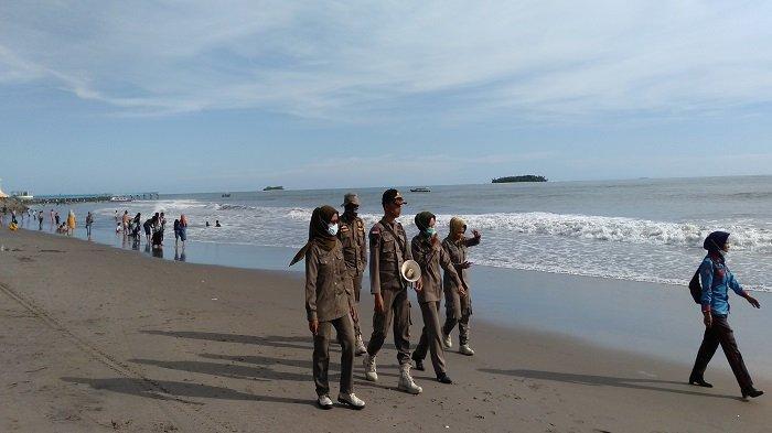 Sejumlah Petugas Satpol PP Kota Pariaman saat memberikan imbauan kepada pengunjung untuk mengurangi aktivitas mandi di pantai sekaligus objek wisata setempat pada Selasa (1/6/2021)