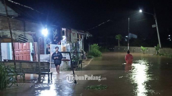Masyarakat saat melintasi banjir di kawasan By Pass Air Pacah, Kecamatan Koto Tangah, Kota Padang, Sumbar, Selasa (28/9/2021).
