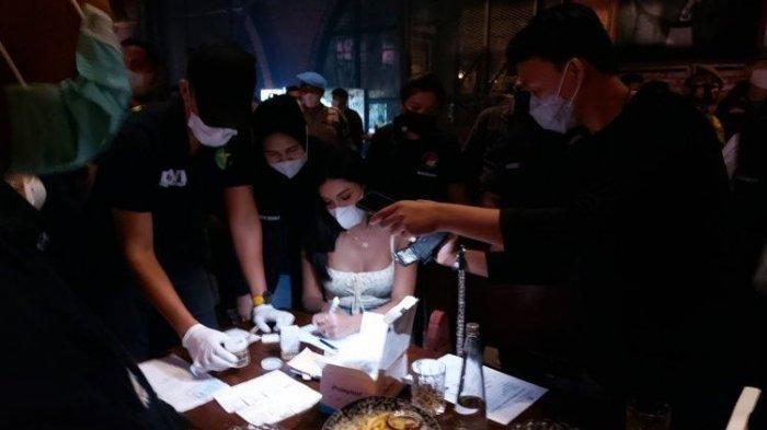 Selebgram Millen Cyrus (tengah) jalani tes urine saat terjaring razia protokol kesehatan yang dilaksanakan oleh Direktorat Reserse Narkoba Polda Metro Jaya di Bar Brotherhood Gunawarman, Kebayoran Baru, Jakarta Selatan, Minggu dini hari (28/2/2021).
