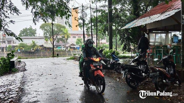 Pengendara sepeda motor saat melewati hujan di Kota Padang, Sumbar.