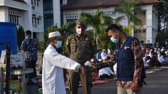 Satgas Covid-19 Pariaman melakukan pengecekan suhu tubuh pada jamaah yang hendak shalat Idul Fitri di Balai Kota Pariaman, Kamis (13/5/2021).